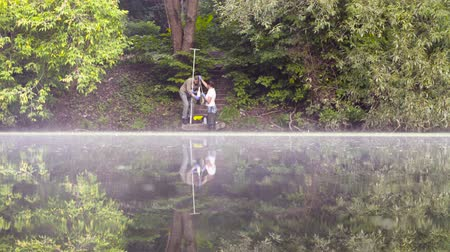 conservationist : Two ecologist getting samples of water in city park Stock Footage