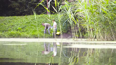 conservationist : Two ecologist getting soil samples from the bottom of the lake Stock Footage