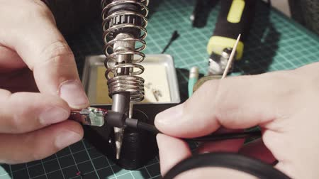 soldering iron : Male hands repairing wire for electronic devices.