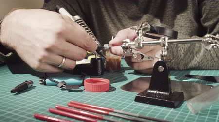 cutting mat : Male hands repairing wire for electronic devices.