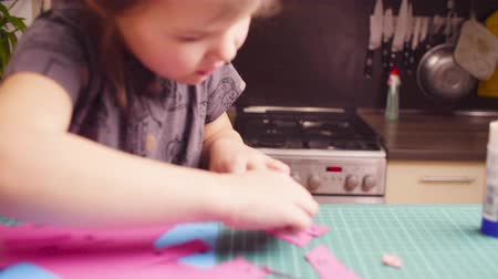 scrapbook : Little girl glueing colored paper