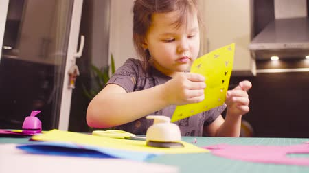 scrapbook : Little girl glueing and cutting colored paper