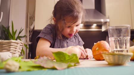 cutting mat : Little girl sitting at the desk makes necklace of acorns Stock Footage