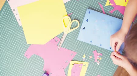 scrapbook : Hands of little girl gluing colored paper