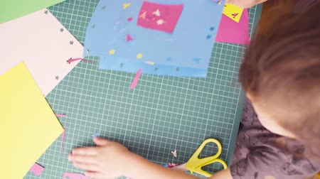 album de recortes : Little girl cutting colored paper with scissors