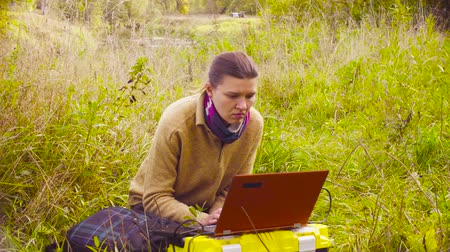 ツールボックス : Woman scientist ecologist working on a laptop in the forest 動画素材