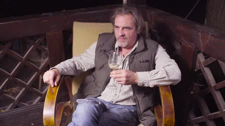 middle age : Senior man sitting in a chair drinking wine and smoking Stock Footage