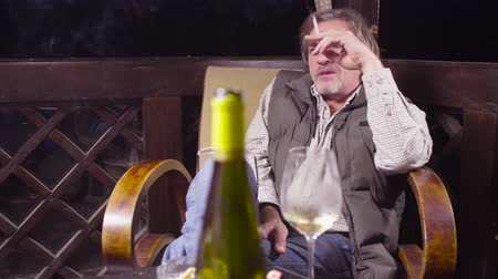 harmful : Senior man sitting in a chair drinking wine and smoking Stock Footage