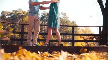 Legs of a couple dancing on the wooden bridge