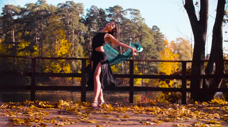 A woman with a stole in her hands dancing on the bridge alone