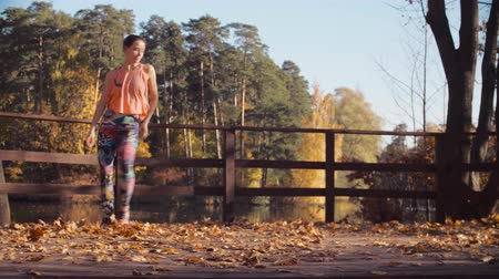 golden falls : Young attractive woman dancing on the bridge alone Stock Footage