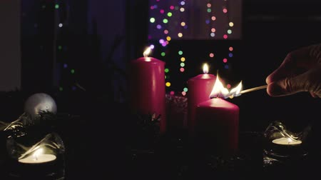 pan shot : Female hands lighting candles in dark room Stock Footage