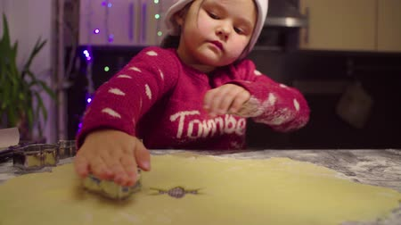pan shot : Little girl carves Christmas cookies