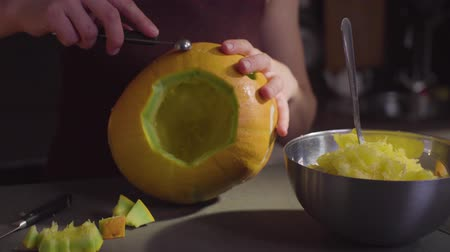 pan shot : Female hands carves from a pumpkin Jack-o-lantern for Halloween celebration Stock Footage