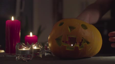 salva : A female hand places a candle in a Jack-o-lantern.