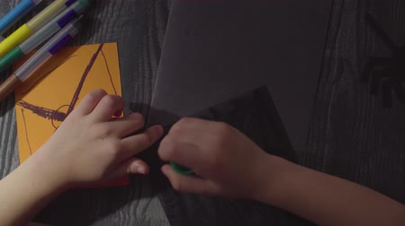 паук : Girls hands glueing a card. Preparing for the celebration of Halloween
