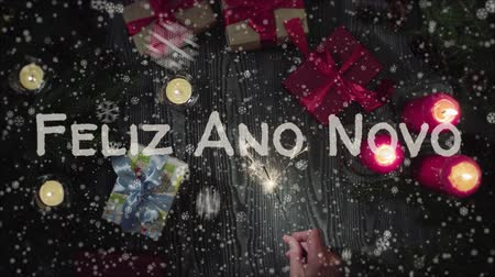list : Animation Feliz Ano Novo - Happy New Year in portuguese, female hand holding a sparkler