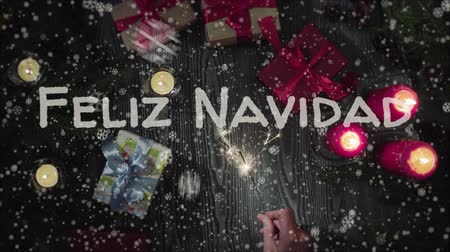 Навидад : Animation Feliz Navidad - Merry Christmas in spanish, female hand holding a sparkler