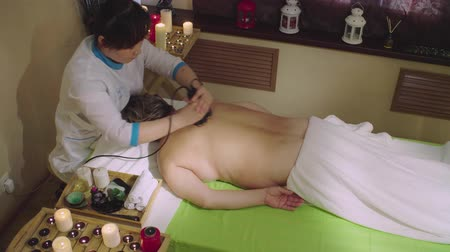 massager : Young chinese doctor doing massage to a senior woman