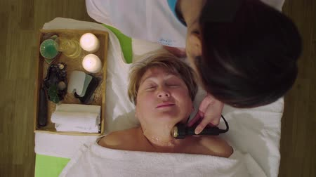 massager : Young chinese doctor doing cosmetic massage to a senior woman Stock Footage