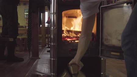 conveniência : Male hand putting firewood in the stove