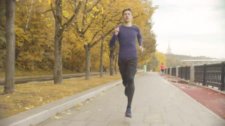 szybko : Young man running fast along the road in the park
