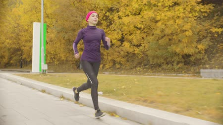 follow shot : Young sportswoman running along the road Stock Footage