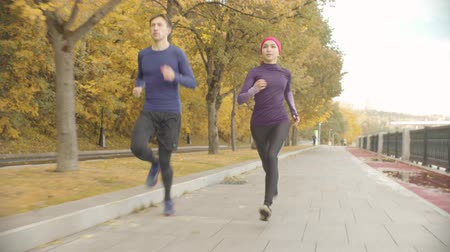 follow shot : Young sportswoman and sportsman running along the road Stock Footage