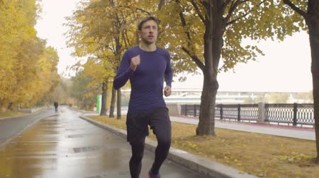 follow shot : Young man running along the road in the park Stock Footage