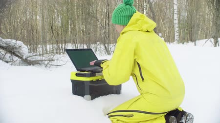 environmentalist : Ecologist in sportswear working on the laptop in winter forest Stock Footage