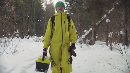 environmentalist : Ecologist with the dog walking along the road in winter forest