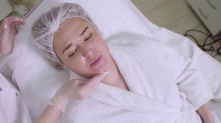 mezoterapia : Beautician cleans clients face after mesotherapy procedure Wideo