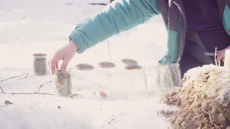 маркировка : Ecologist prepares glass jars for samples and marks them