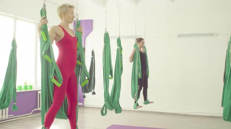 meia idade : Gravity yoga. Two women doing exercises in hammocks