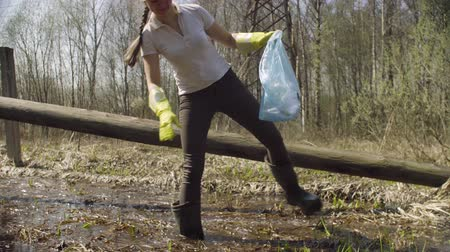 coletando : Woman volunteer collecting garbage in the pond