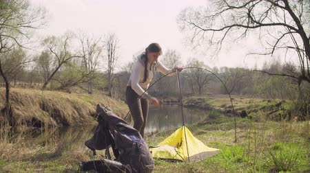 namiot : Woman putting up a tourist tent in the forest Wideo