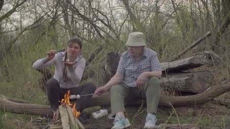 espetos : Two women roasting marshmallows on a fire