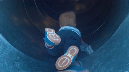 legs only : A child lying on the belly on the childrens slide Stock Footage