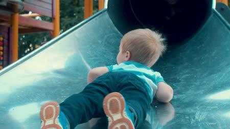 legs only : A child playing on a childrens slide Stock Footage