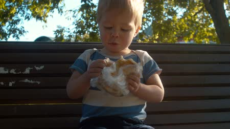 children only : Little boy sitting on a bench and eating bun