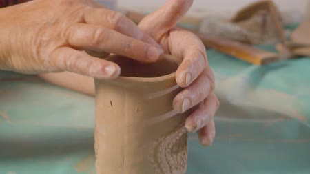 terrakotta : Senior female hands aligns the edge of the clay mug Stock mozgókép