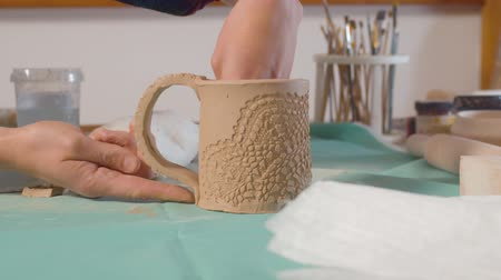 terrakotta : Young woman attaches the handle to the mug