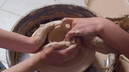 cserépedény : Womans hands making a pot on a potters wheel