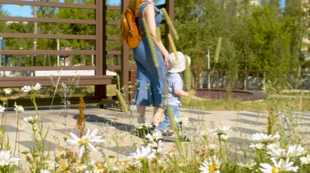 canteiro de flores : Baby boy and his mom walking along the road in the park