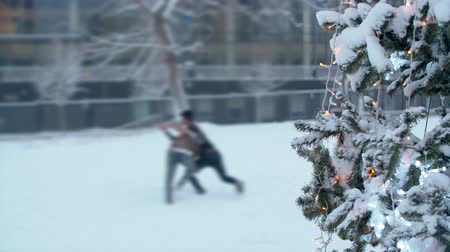 Teenagers playing snowballs near a Christmas tree. Christmas tree outdoors under the snow. City holiday decorations. Snowfall in the city.