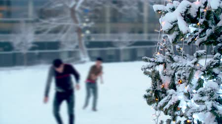ziyafet : Teenagers playing snowballs near a Christmas tree. Christmas tree outdoors under the snow. City holiday decorations. Snowfall in the city.