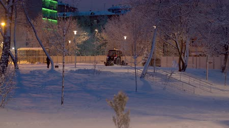 recentemente : Tractor grader working in the snow covered park. Snow shines beautifully in the lights of latternes. Winter magic evening. Trees covered by fresh snow Vídeos