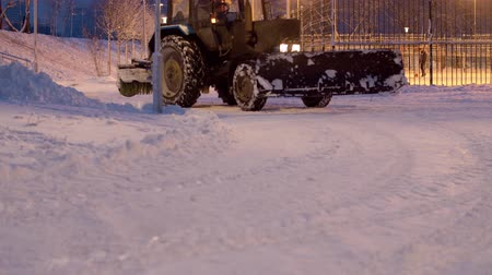 трактор : Tractor grader working in the snow covered park. Snow shines beautifully in the lights of latternes