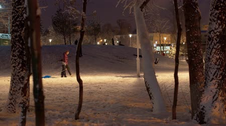 Children riding down a hill in snow covered city park. Fresh snow, magical winter evening. Unrecognizable people on the stroll after snowfall.