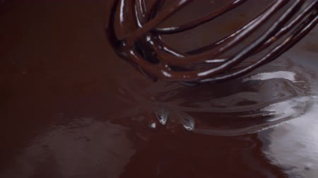 помадка : Mixing melted dark chocolate. Close up of liquid hot chocolate flows from a whisk. Confectionery Confectioner prepares dessert, sauce.